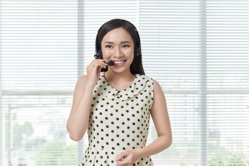 De gelukkige glimlachende vrolijke exploitant van de steuntelefoon in hoofdtelefoon stock foto