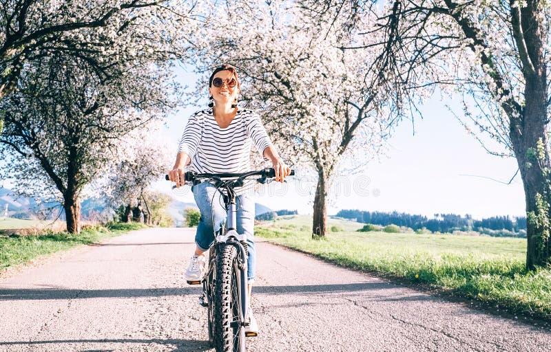 De gelukkige glimlachende vrouw berijdt een fiets op de landweg onder bl stock fotografie