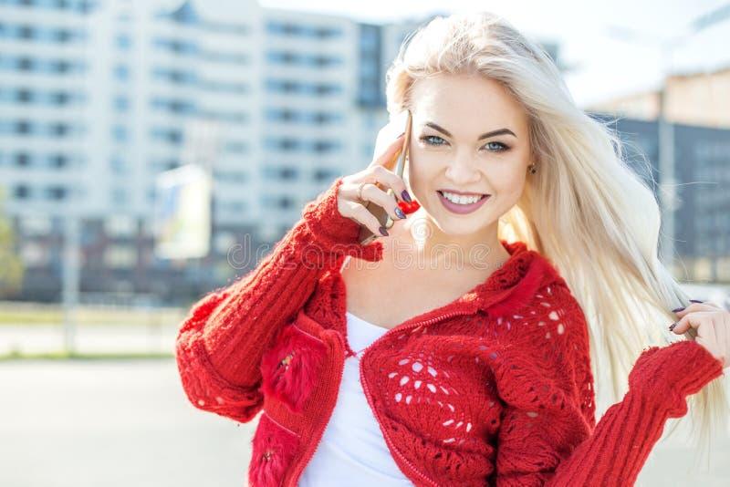 De gelukkige glimlachende vrouw die een rode sweater dragen spreekt op een celtelefoon stock afbeelding