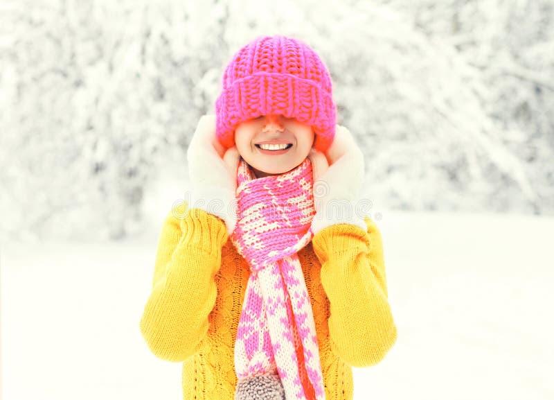De gelukkige glimlachende vrouw die van de manierwinter een kleurrijke gebreide hoed dragen die pret over sneeuw hebben royalty-vrije stock afbeelding