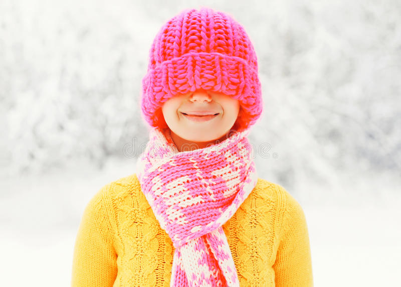 De gelukkige glimlachende vrouw die van de manierwinter kleurrijke gebreide hoed dragen die pret over sneeuw hebben royalty-vrije stock fotografie
