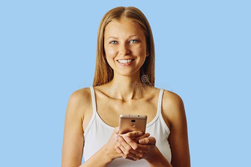 De gelukkige glimlachende vrouw houdt haar cellphone, over blauwe achtergrond stock foto