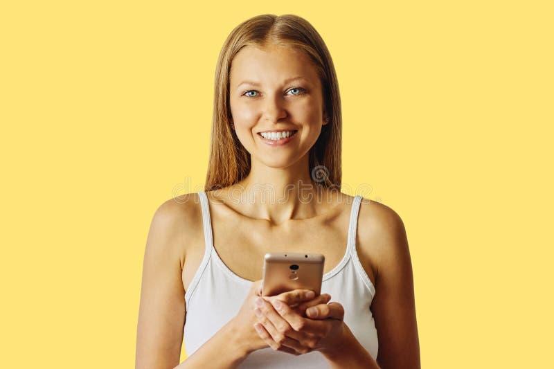 De gelukkige glimlachende vrouw houdt haar cellphone, over gele achtergrond royalty-vrije stock foto