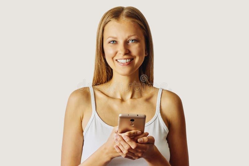 De gelukkige glimlachende vrouw houdt haar die cellphone, over lichtgrijze achtergrond wordt geïsoleerd stock fotografie