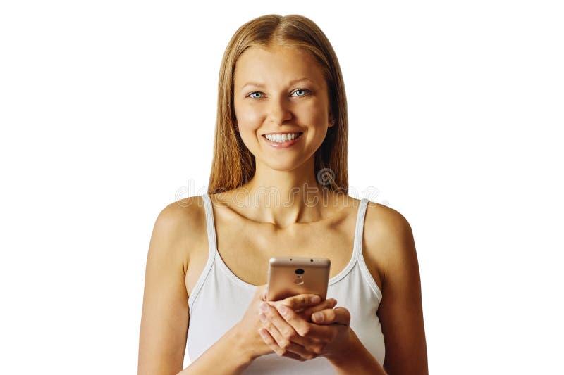 De gelukkige glimlachende vrouw houdt haar die cellphone, over witte achtergrond wordt geïsoleerd royalty-vrije stock foto's