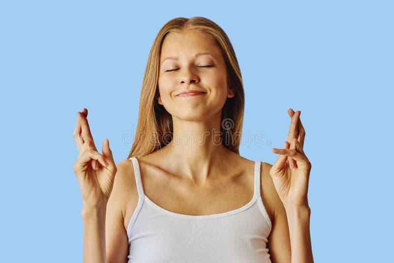 De gelukkige glimlachende vrouw houdt vingers gekruist en wenst een goed geluk dit royalty-vrije stock afbeeldingen