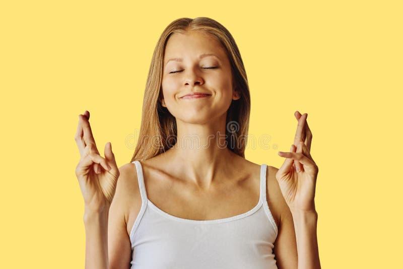 De gelukkige glimlachende vrouw houdt vingers gekruist en wenst een goed geluk dit royalty-vrije stock fotografie