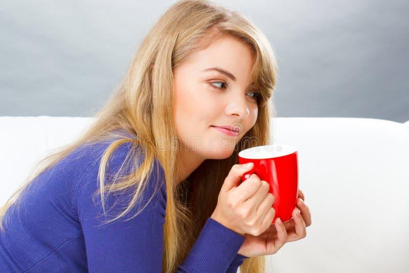 De gelukkige glimlachende vrouw met kop thee of koffie, ontspant thuis royalty-vrije stock foto's