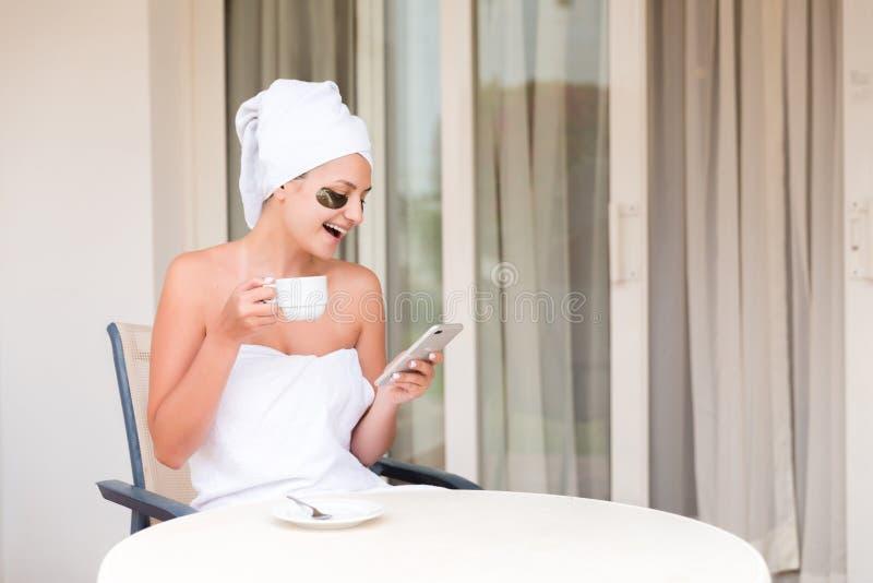 De gelukkige glimlachende vrouw in onder-oog herstelt readind sms bericht en het drinken koffie bij de toevlucht van het hotelter royalty-vrije stock foto