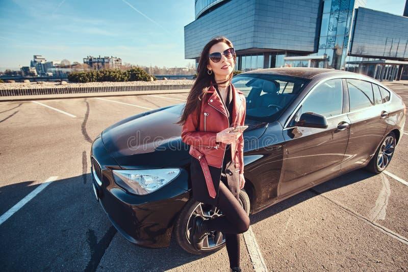 De gelukkige glimlachende vrouw in rode jasje en zonnebril leunt op haar auto terwijl het babbelen op mobiele telefoon stock fotografie