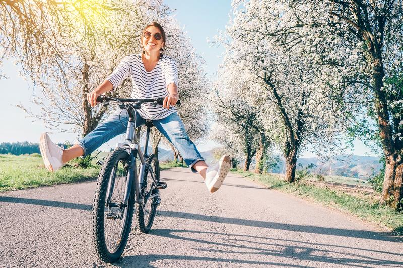 De gelukkige glimlachende vrouw spreidt cheerfully benen op fiets op de landweg onder bloesembomen uit De lente is komend concept stock foto