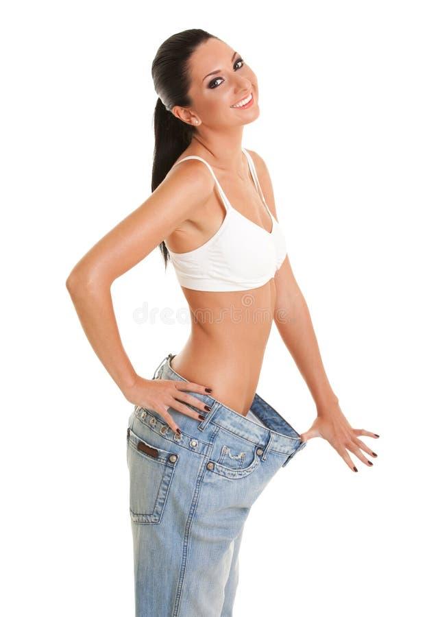 De gelukkige glimlachende vrouw toont haar gewichtsverlies door oude jeans te dragen stock afbeelding