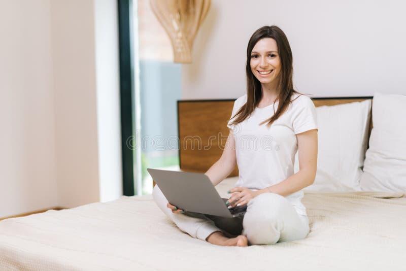 De gelukkige glimlachende vrouw zit op bed, bekijkt camera en gebruikt laptop royalty-vrije stock fotografie
