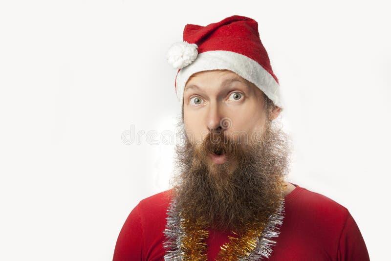 De gelukkige grappige Kerstman met echte baard en rode hoed en overhemd die gek gezicht en het glimlachen, het kijken en camera m stock fotografie
