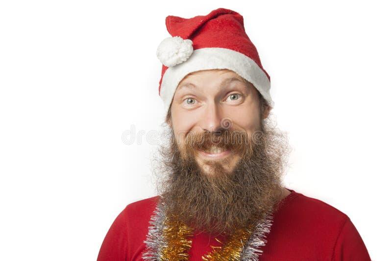 De gelukkige grappige Kerstman met echte baard en rode hoed en overhemd die gek gezicht en het glimlachen, het kijken en camera m stock foto