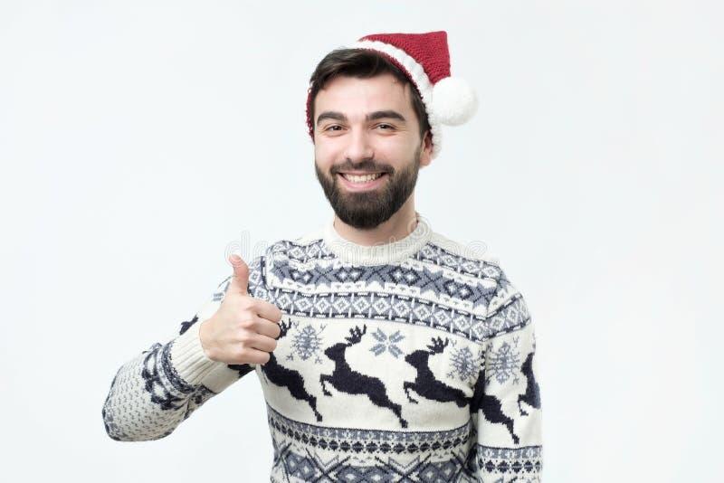 De gelukkige grappige mens in rode Kerstmishoed toont duimen en goed geluk royalty-vrije stock afbeelding