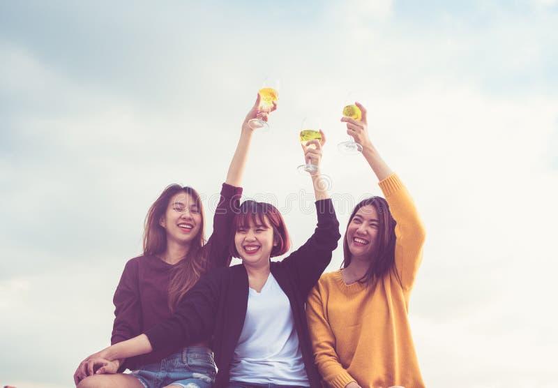 De gelukkige groep Aziatische meisjesvrienden geniet van lachend en vrolijk mousserende wijnglas bij dakpartij, feestelijke Vakan stock afbeeldingen