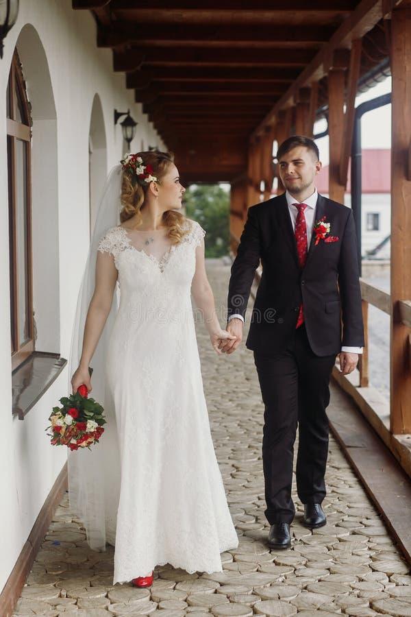 De gelukkige handen van de bruidholding met bruidegom, mooie blonebruid in w stock foto