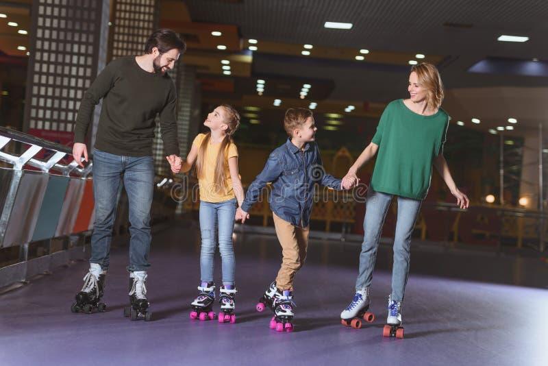 de gelukkige handen van de familieholding terwijl samen het schaatsen stock foto