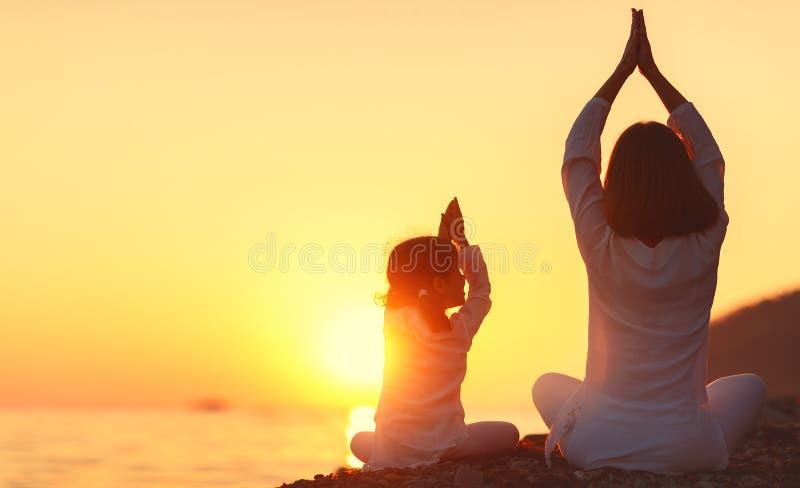 De gelukkige het familiemoeder en kind die yoga doen, mediteren in lotusbloemposi royalty-vrije stock foto