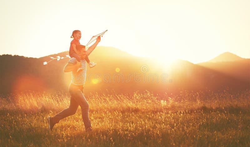 De gelukkige het familievader en kind lopen op weide met een vlieger in summe stock afbeelding