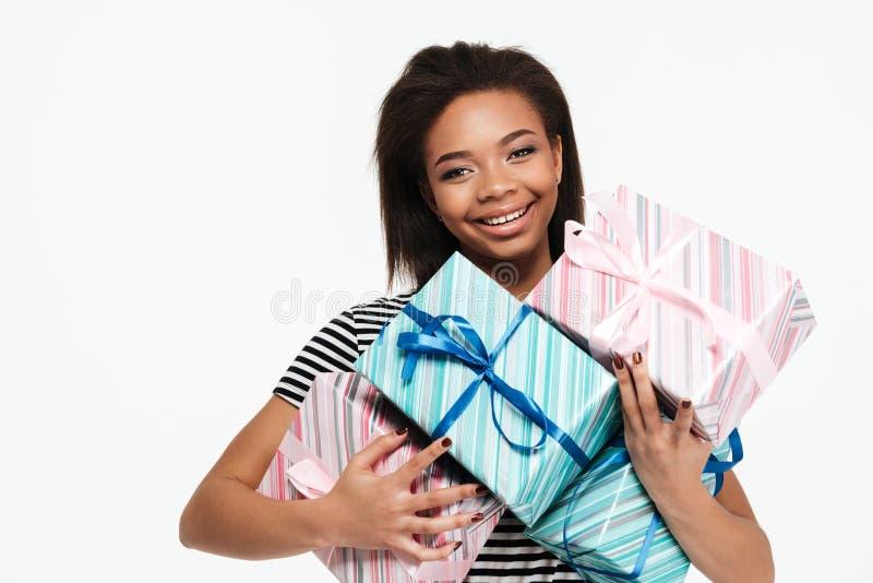 De gelukkige het glimlachen Afrikaanse stapel van de vrouwenholding huidige dozen royalty-vrije stock afbeeldingen