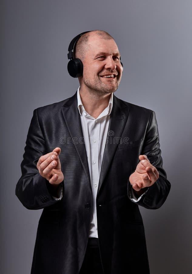 De gelukkige het glimlachen emotionele dansende en zingende kale mens die de muziek in draadloze hoofdtelefoon en de handen tonen stock foto's