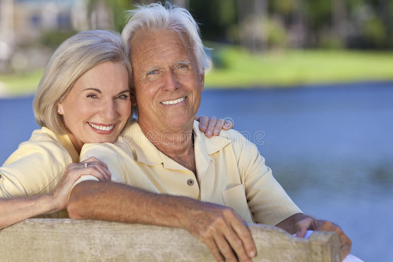 De gelukkige het Glimlachen Hogere Zitting van het Paar op de Bank van het Park stock afbeeldingen