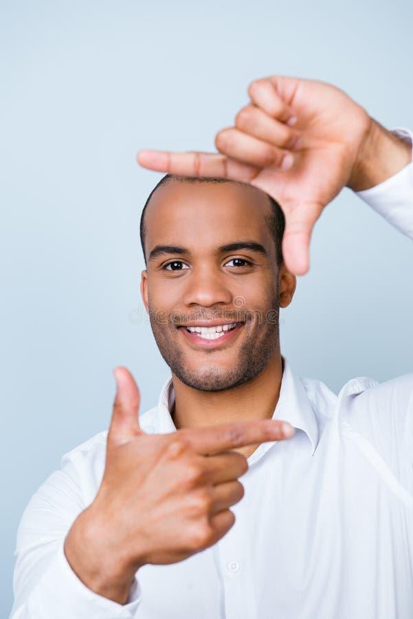 De gelukkige het glimlachen jonge Afrikaanse kerel maakt kader met vingers, hij stock foto's