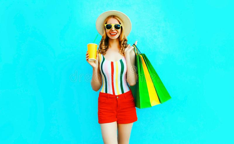 De gelukkige het glimlachen kop van de vrouwenholding van vruchtensap met het winkelen zakken in kleurrijke t-shirt, de hoed van  stock foto