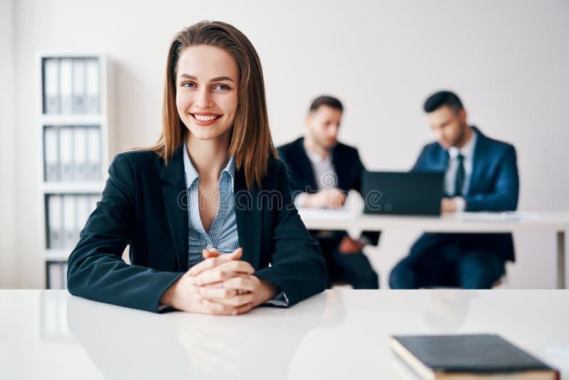 De gelukkige het glimlachen zitting van het bedrijfsvrouwenportret in bureau met haar commercieel team op achtergrond stock afbeeldingen