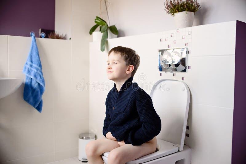 De gelukkige het glimlachen zitting van de 6 éénjarigenjongen op het toilet royalty-vrije stock fotografie