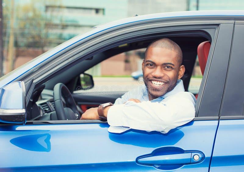 De gelukkige het glimlachen zitting van de jonge mensenkoper in zijn nieuwe auto royalty-vrije stock foto's