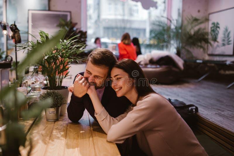 De gelukkige het houden van kerel houdt en bijt de handzitting van zijn meisje bij de lijst in de koffie en bekijkt haar stock afbeeldingen