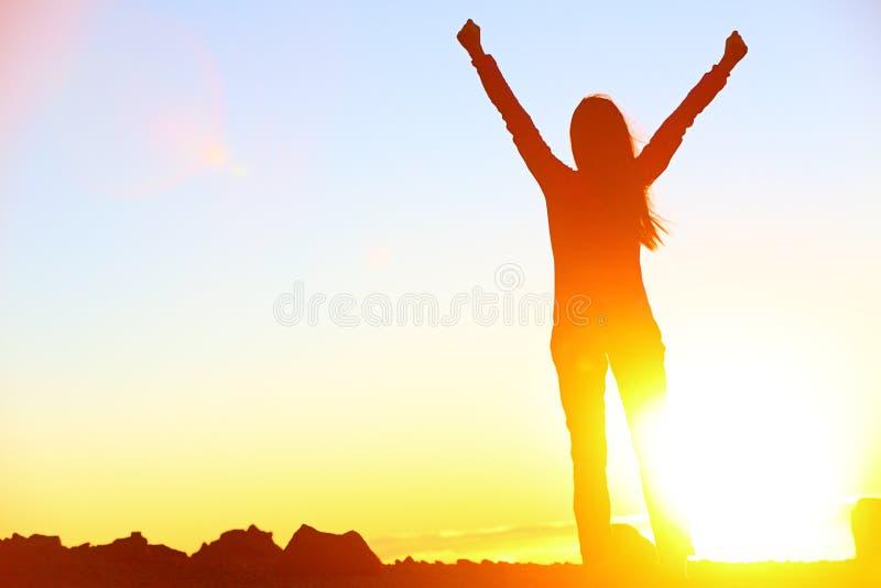 De gelukkige het vieren het winnen zonsondergang van de succesvrouw stock foto's