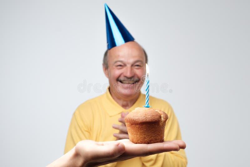 De gelukkige hogere mens in birtyday hoed is happpy om kleine cake met één kaars te ontvangen stock fotografie