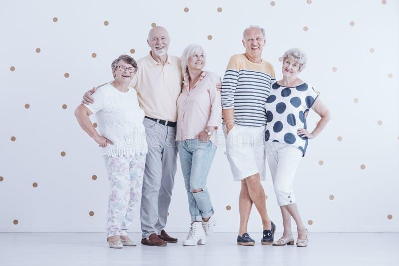 De gelukkige hogere paren die van vergadering genieten tegen witte muur met gaan royalty-vrije stock afbeeldingen