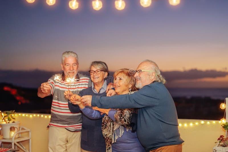 De gelukkige hogere vrienden die verjaardag met sterretjes vieren speelt openlucht mee - Oudere mensen die pret in terras in de d stock afbeeldingen