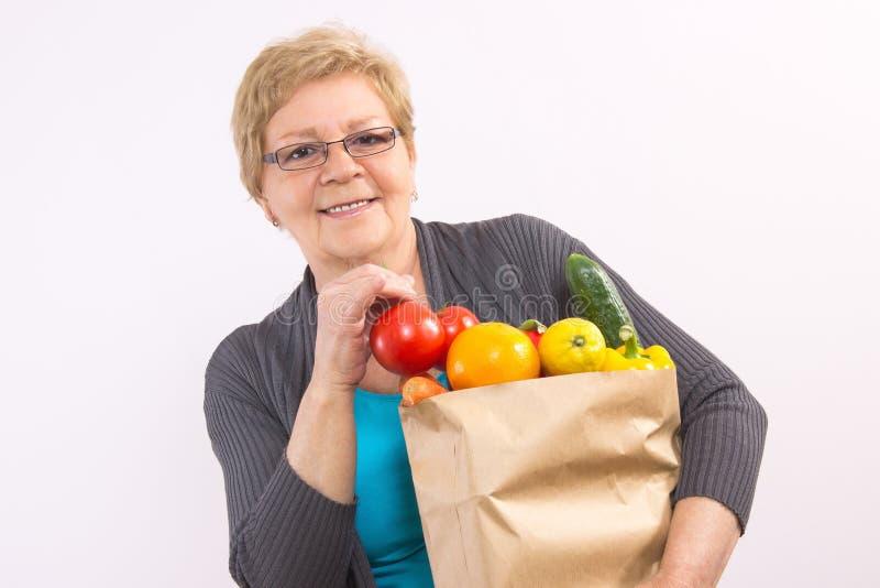 De gelukkige hogere vruchten en de groenten van de vrouwenholding in het winkelen zak, gezonde voeding in oude dag stock fotografie