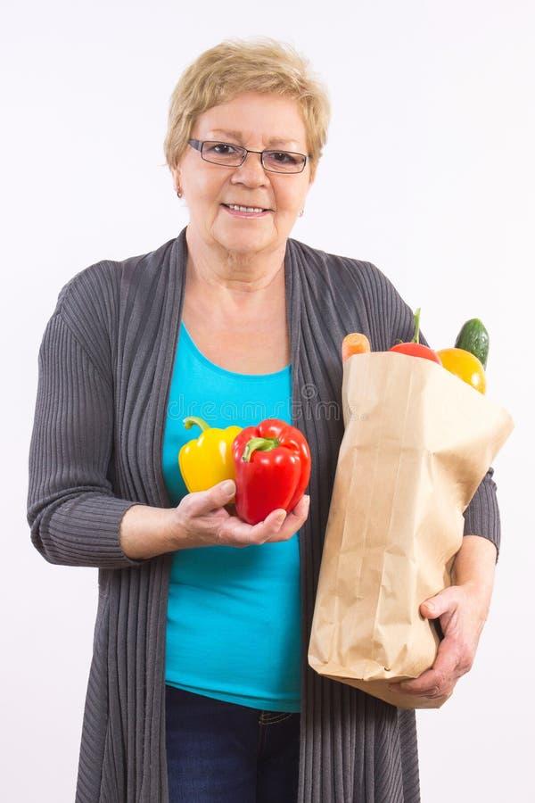 De gelukkige hogere vruchten en de groenten van de vrouwenholding in het winkelen zak, gezonde voeding in oude dag royalty-vrije stock afbeeldingen