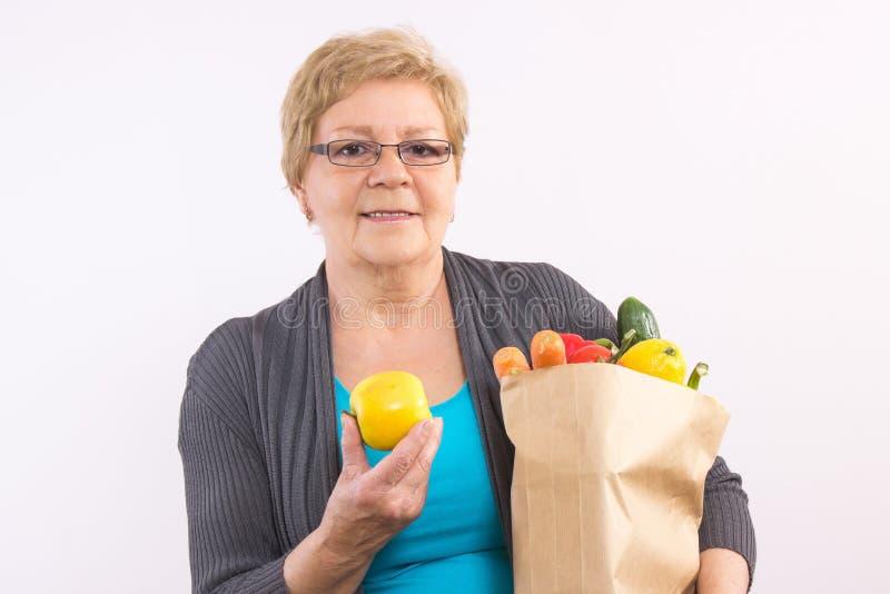 De gelukkige hogere vruchten en de groenten van de vrouwenholding in het winkelen zak, gezonde voeding in oude dag stock foto