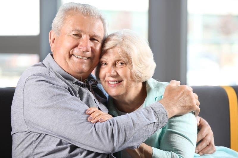 De gelukkige Hogere Zitting van het Paar op Bank thuis stock fotografie