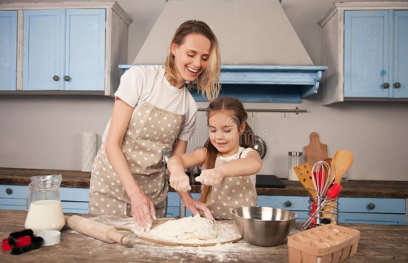 De gelukkige houdende van familie bereidt samen bakkerij voor Moeder en kind het dochtermeisje maakt binnen koekjes en heeft pret royalty-vrije stock foto's
