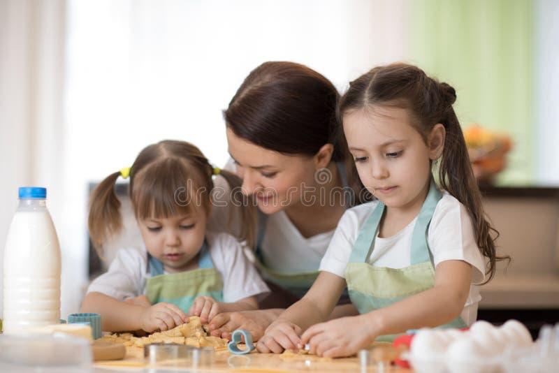 De gelukkige houdende van familiemoeder en de dochters bereiden samen bakkerij voor Het mamma en de kinderen koken koekjes en heb stock fotografie
