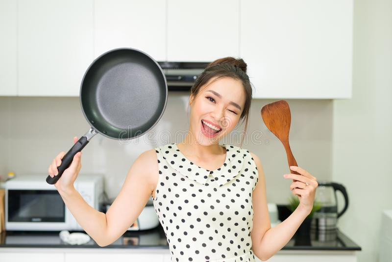 De gelukkige huisvrouw steunt met pan houten keerder in keuken royalty-vrije stock afbeelding