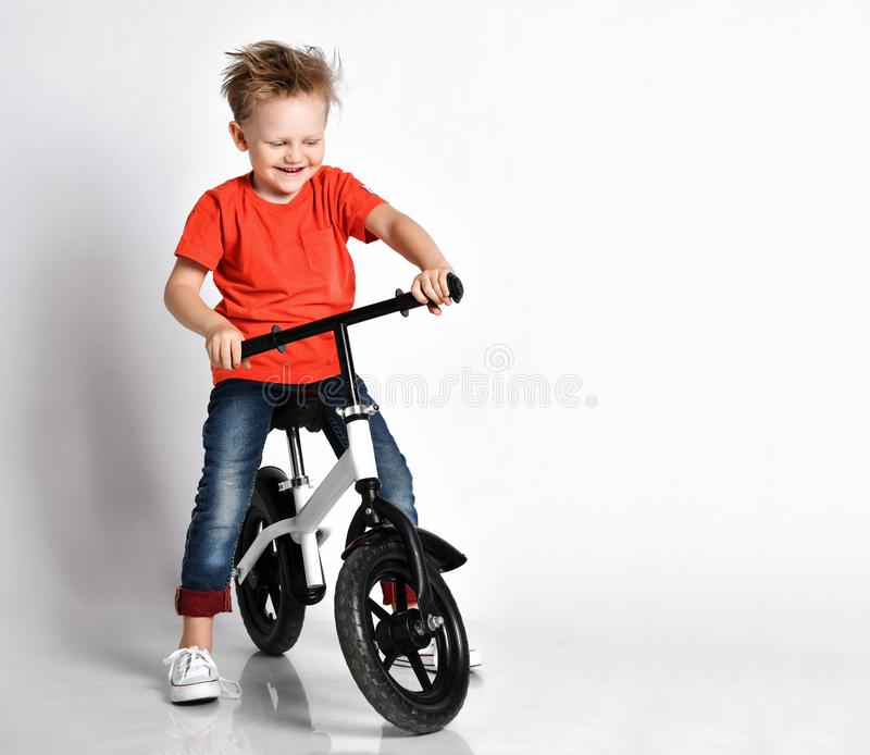 De gelukkige jong geitjejongen in oranje t-shirt en jeans probeert om zijn nieuwe fiets zonder pedalen te berijden Hij test het h royalty-vrije stock afbeelding