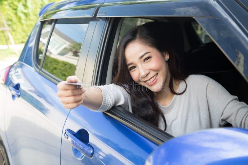 De gelukkige jonge Aziatische betaalkaart van de vrouwenholding of creditcard en gebruikt om voor benzine, diesel, en andere bran stock afbeeldingen