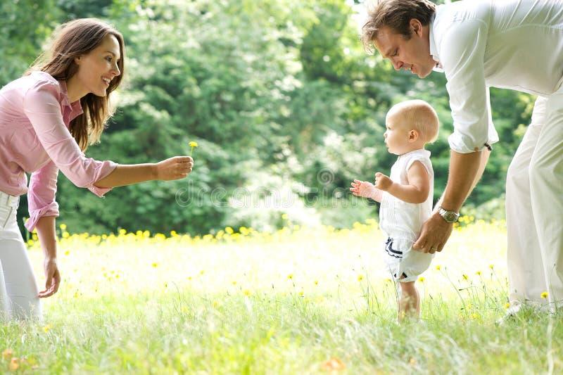 De gelukkige jonge baby van het familieonderwijs om te lopen stock afbeeldingen