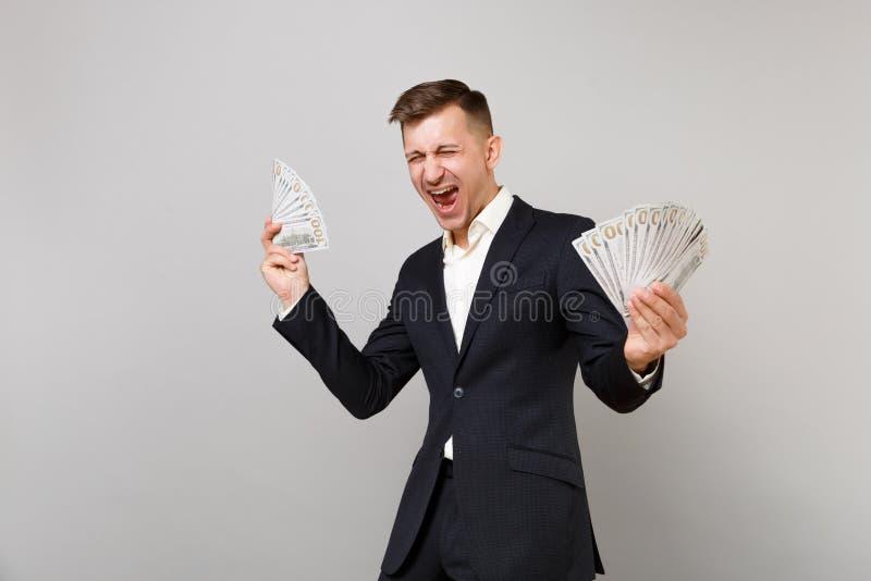 De gelukkige jonge bedrijfsmens in de klassieke zwarte kostuum het gillen bos van holdingspartijen van dollarsbankbiljetten int g stock foto's