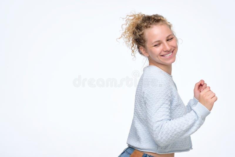 De gelukkige jonge blonde krullende vrouw met grote glimlach is teruggekeerd royalty-vrije stock fotografie